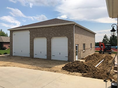 "Custom Three Car Detached Garage - 40x50, hip roof, 15' tall walls, all brick, 12"" overhangs, 1- 14x14 overhead door, 2 - 8x9 overhead doors"